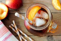 Mason jar of peach iced tea on wood, downward view. Mason jar glass of homemade peach iced tea on a rustic wooden background, downward view stock image
