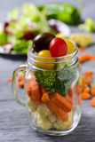 Mason jar salad. A salad with a mix of different vegetables, such as cauliflower, carrot, broccoli and cherry tomatoes of different colors served in a mason jar royalty free stock photo