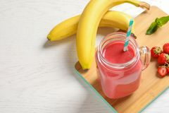 Mason jar with tasty strawberry smoothie. On wooden board royalty free stock photo