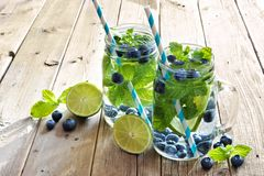 Mason jars of blueberry, lime, mint detox water against wood Royalty Free Stock Image