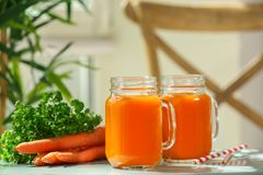 Mason jars of carrot juice. On table royalty free stock image