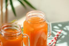 Mason jars of carrot juice. On table royalty free stock photo