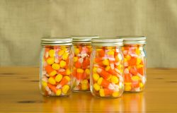 Mason jars filled with candy corn. Four mason jars filled with candy corn on a wooden table Stock Images
