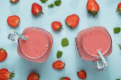 Mason jars with strawberry smoothie of milkshake on blue table with berries halfs. royalty free stock images