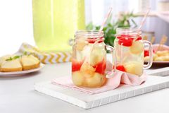 Mason jars with tasty melon and watermelon ball drink. On light table stock image