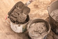 Mason kneads cement mortar for pouring concrete screed royalty free stock photo