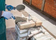 Mason made a wall. Mason holds fangli and jointer while building a wall with cement Stock Photos