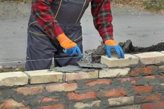 Worker building brick wall using trowel. Mason making wall with mortar and bricks, using trowel tool Royalty Free Stock Photography