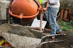 A mason is pouring water into the cement mixer stock photo