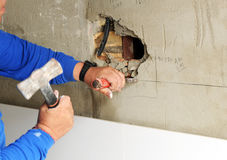 Mason Preparing The Hole In The Wall To Place A Box Electrical Outlets For The Renovation Of The House Stock Photo