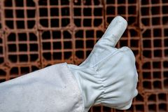 Mason with protective gloves making a positive gesture. Mason with protective gloves, PPE, making a positive gesture with his thumb, at construction site. Sao stock images