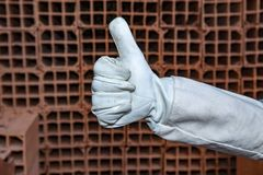 Mason with protective gloves making a positive gesture. Mason with protective gloves, PPE, making a positive gesture with his thumb, at construction site. Sao stock image