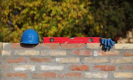 Construction worker equipment at brick wall. Mason tool and equipment at brick wall, level tool, gloves and helmet, construction site Royalty Free Stock Photography