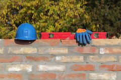 Construction worker equipment at brick wall. Mason tool and equipment at brick wall using, level tool, gloves and helmet Stock Images
