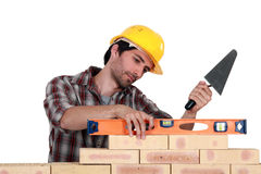 A mason using a level. To check his wall Royalty Free Stock Photo