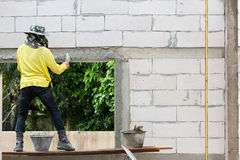 Mason using trowel for plastering the concrete to build wall, Co Stock Photos