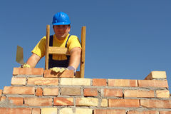 Mason at work. Mason building brick wall standing on wooden ladder stock image