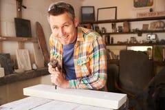 Mason At Work On Carving di pietra in studio fotografia stock