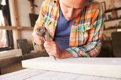 Mason At Work On Carving en pierre dans le studio Photo stock