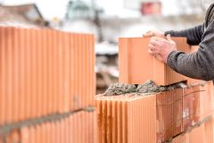 Mason worker bricklayer installing brick walls Stock Image