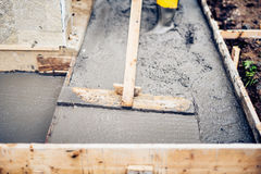 Mason worker building and leveling a first layer of fresh concrete floor at house stairs and sidewalks, construction site Royalty Free Stock Photos
