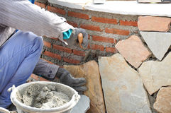 Mason worker installing flagstones on brick wall w Royalty Free Stock Images