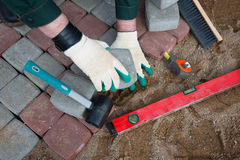 Mason worker making sidewalk pavement Stock Images