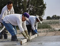 Masonry concrete workers  place and screed wet concrete to form Stock Photo