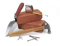 Masonry construction. Bricks, trowel, hammer & measuring tape on white Stock Photography
