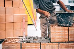 Masonry, industrial brick mason, bricklayer working on building exterior walls at construction site royalty free stock images
