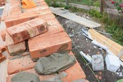 masonry Lägga tegelstenväggen på huskonstruktionsplats med betong arkivfoton