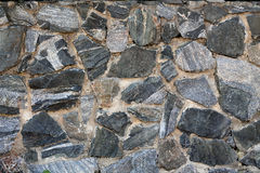 Masonry made of granite stone. Background. Wall is built of granite stone bonded with cement Stock Images