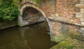 Masonry stone arch in the ancient Dutch city of Delft. Brick masonry arch above a canal in the historic town of Delft in the Netherlands. It is a cloudy day at Royalty Free Stock Image