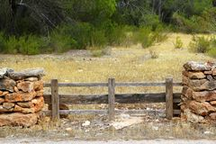 Masonry stone wall wooden fence pine forest Stock Photo
