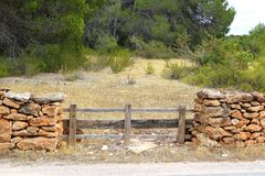 Masonry stone wall wooden fence pine forest Royalty Free Stock Photography