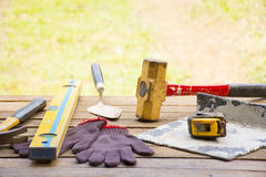 Masonry tool background such as glove and tape measure and sledgehammer with trowel and level and etc.Background  craftsman tool. Masonry tool background for Royalty Free Stock Image