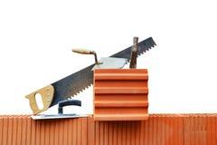 Masonry tools on a brick wall. Royalty Free Stock Photos