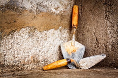 Masonry trowels on a concrete wall Stock Photography
