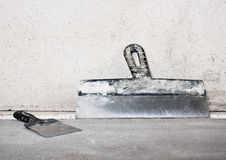 Masonry trowels near a grey plaster wall Stock Photos