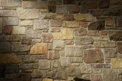 Masonry Wall of Multicolored Stone Lit Diagonally Stock Images