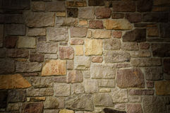 Masonry Wall of Multicolored Stone Lit Dramatically Royalty Free Stock Image