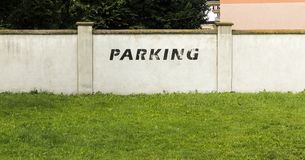 Wall with parking sign next to a lawn Royalty Free Stock Photos