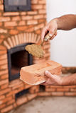 Masonry worker hands with brick and clay mortar on trowel. In front of brick stove Royalty Free Stock Photos