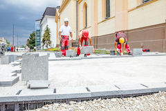 Masons are fitting flagstone, teamwork Royalty Free Stock Photos