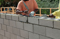 Masons laying a new wall. Bricklayers building a new wall for a house Stock Photo