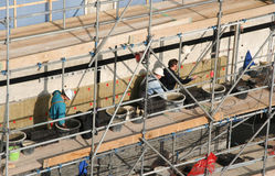 Masons at Work. Three masons on scaffolding at work on a tile wall stock image