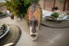 Masque africain placé à un arrangement merveilleux de table dans le style africain image libre de droits