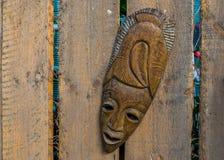 Masque africain traditionnel accrochant sur une barrière en bois, décorations tropicales de jardin, fond indigène photo libre de droits