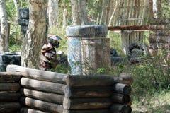 Masque, armes, camouflage du joueur pendant le jeu du paintball Attente de l'ennemi dans l'embuscade Pneus, barils photos stock