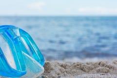 Masque bleu de plongée sur un fond trouble de plage Images stock